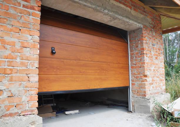 garagentor in backstein haus neubau installieren. - garagentor mit tür stock-fotos und bilder