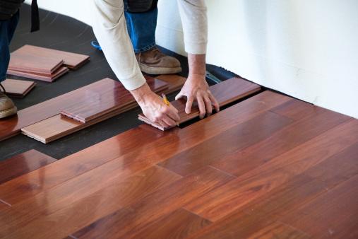 A worker installing hardwood floor in an American upscale home.A worker installing hardwood floor in an American upscale home.