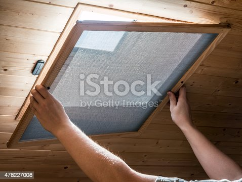 Unrecognizable person is installing a wooden homemade mosquito net attached with magnets, front of an opened velux window on ceiling, in home interior in attic, to prevent flying insects from entering.