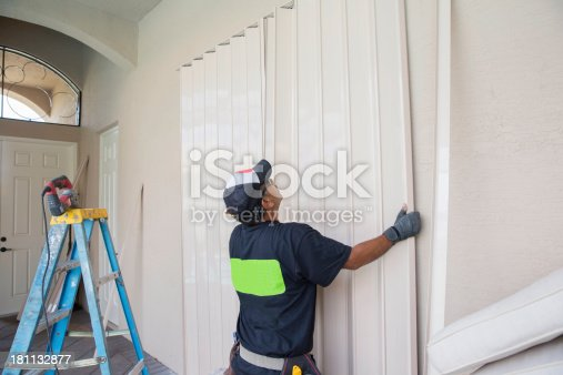 Contractor installing hurricane shutters.  rr