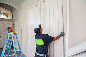 Contractor installing hurricane shutters.  rr