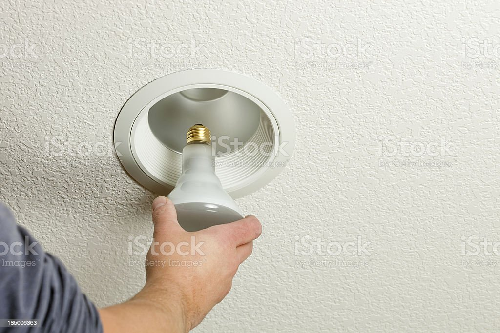 Installing Incandescent Recessed Light Bulb in Ceiling Fixture stock photo