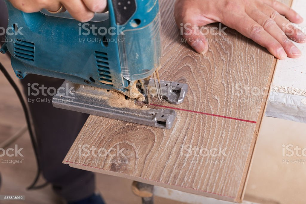 Installing laminate flooring. Carpenter cut parquet floor board stock photo