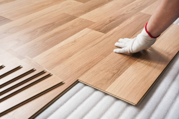 Installing laminated floor, detail on man hand in white glove fitting wooden tile, over white foam base layer stock photo