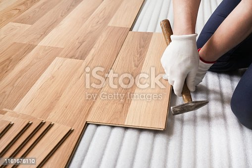 istock Installing laminated floor, detail on man hands fixing one tile with hammer, over white foam base layer 1161676110