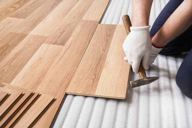 Installing laminated floor, detail on man hands fixing one tile with hammer, over white foam base layer stock photo