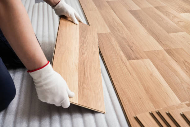 Installing laminated floor, detail on man hands with white gloves fitting wooden tile, over white foam base layer stock photo
