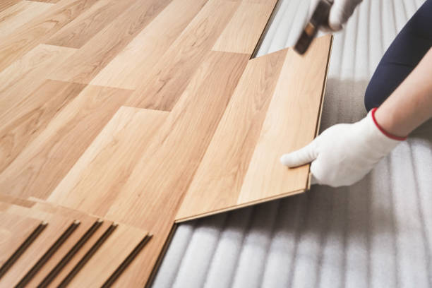 Installing laminated floor, man hand in white glove holding wooden tile and using hammer, over white foam base layer stock photo