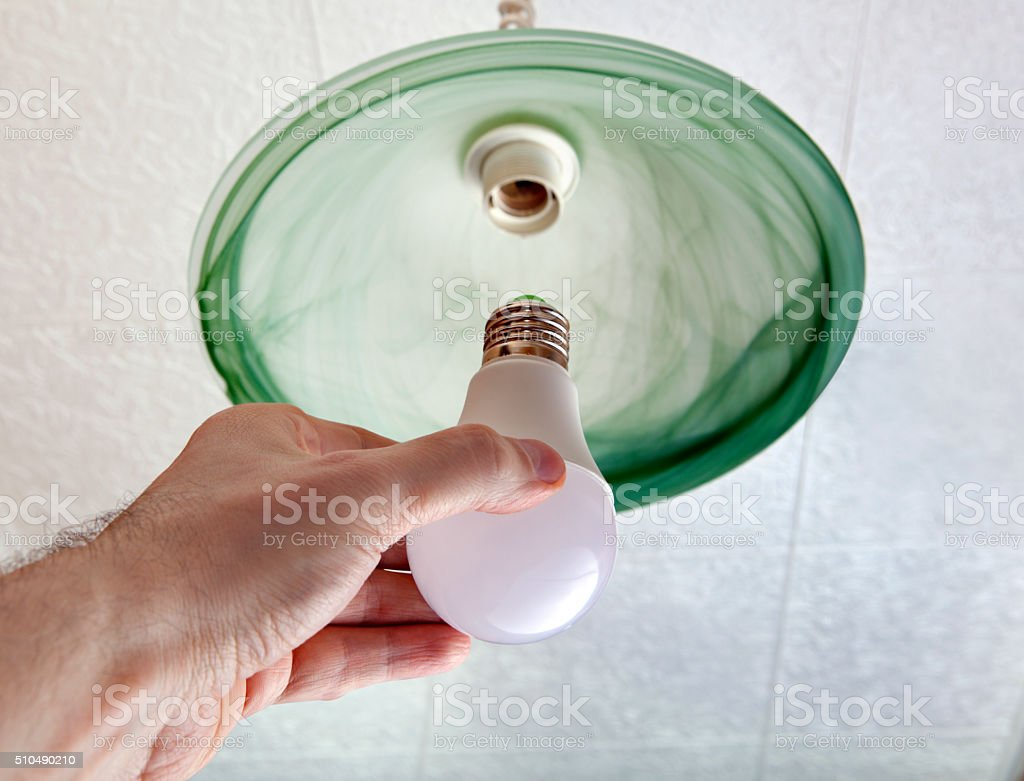 Installing LED light bulb in ceiling light, hand holding lamp. stock photo