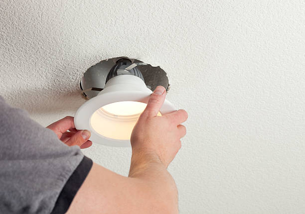 Installing LED Retrofit Bulb into Ceiling Fixture  household fixture stock pictures, royalty-free photos & images