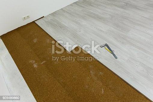 922081754 istock photo Installing light laminate floor with substrate under a laminate on white background 925489860