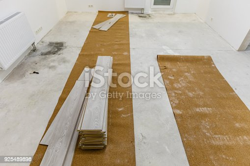 922081754 istock photo Installing light laminate floor with substrate under a laminate on white background 925489898