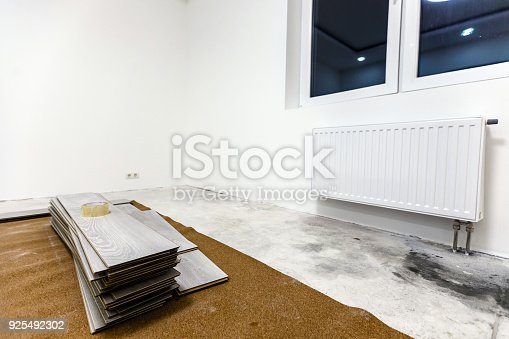 922081754 istock photo Installing light laminate floor with substrate under a laminate on white background 925492302