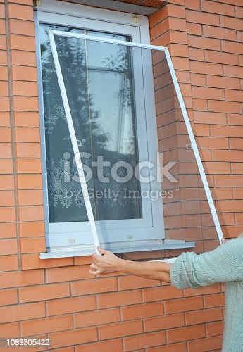 Installing mosquito net,  mosquito wire screen on brick house window.