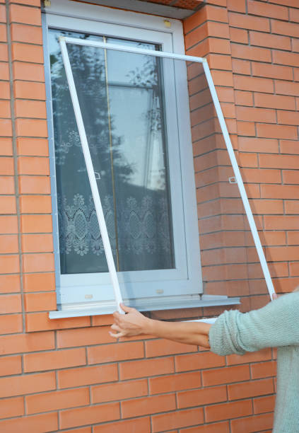 Installing mosquito net,  mosquito wire screen on brick house window. Installing mosquito net,  mosquito wire screen on brick house window. netting stock pictures, royalty-free photos & images
