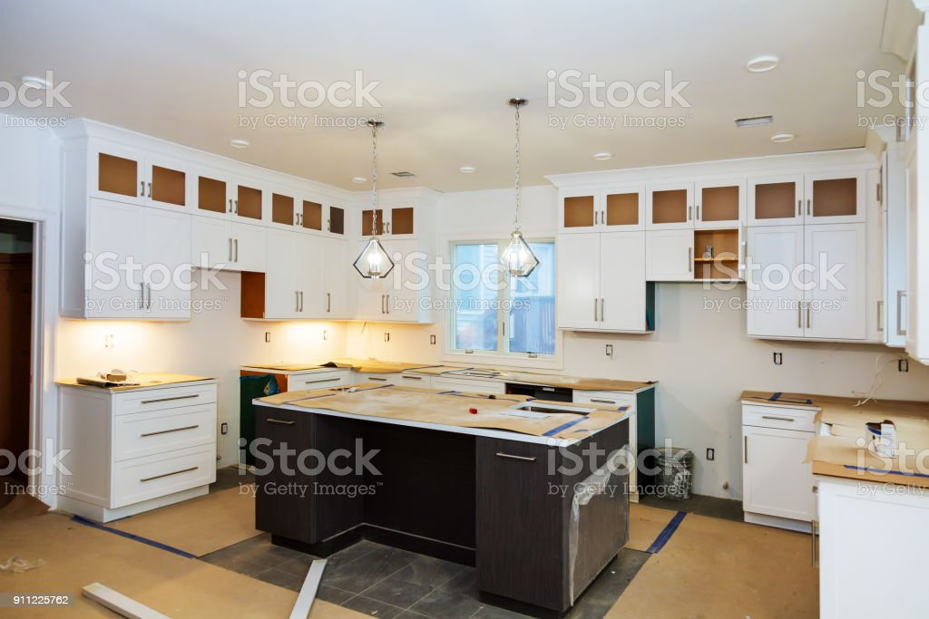 Installing new induction hob in modern kitchen kitchen Installation of kitchen cabinet. stock photo