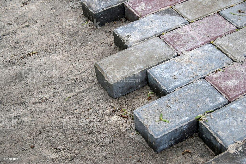Installing paver bricks for the sidewalk pavement stock photo