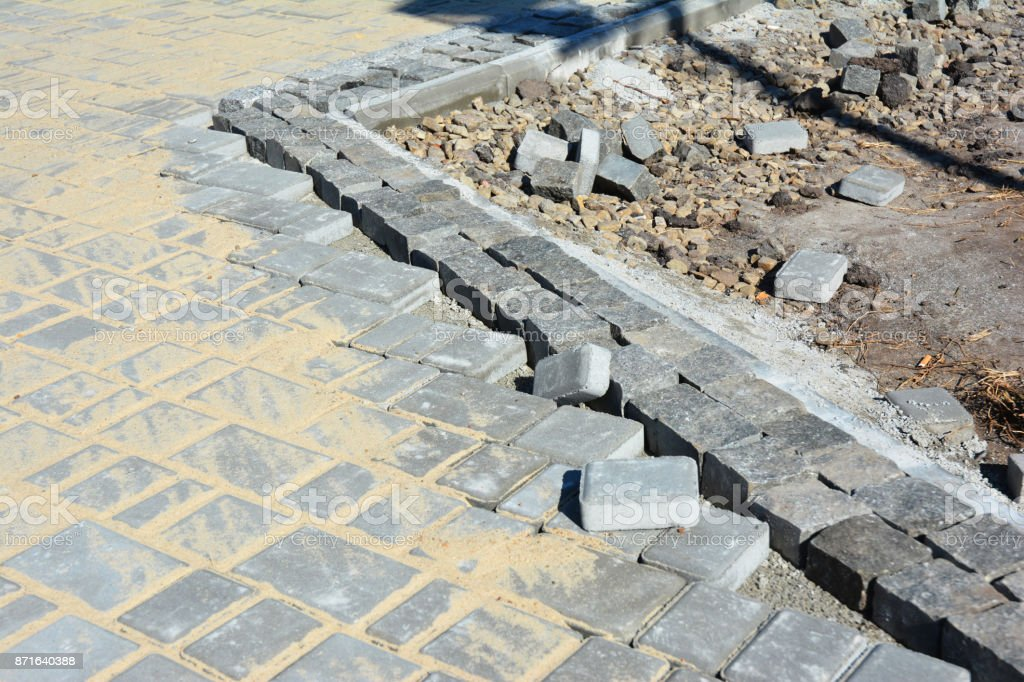 Installing pavers for garden pathway near road curb.  Laying pavement in problem area road curb, kerb stones. stock photo