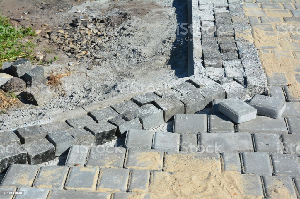 Installing pavers for garden pathway with road curb, kerb stones stock photo