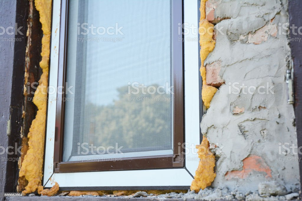 Installing plastic window with mosquito net and insulation foam. stock photo