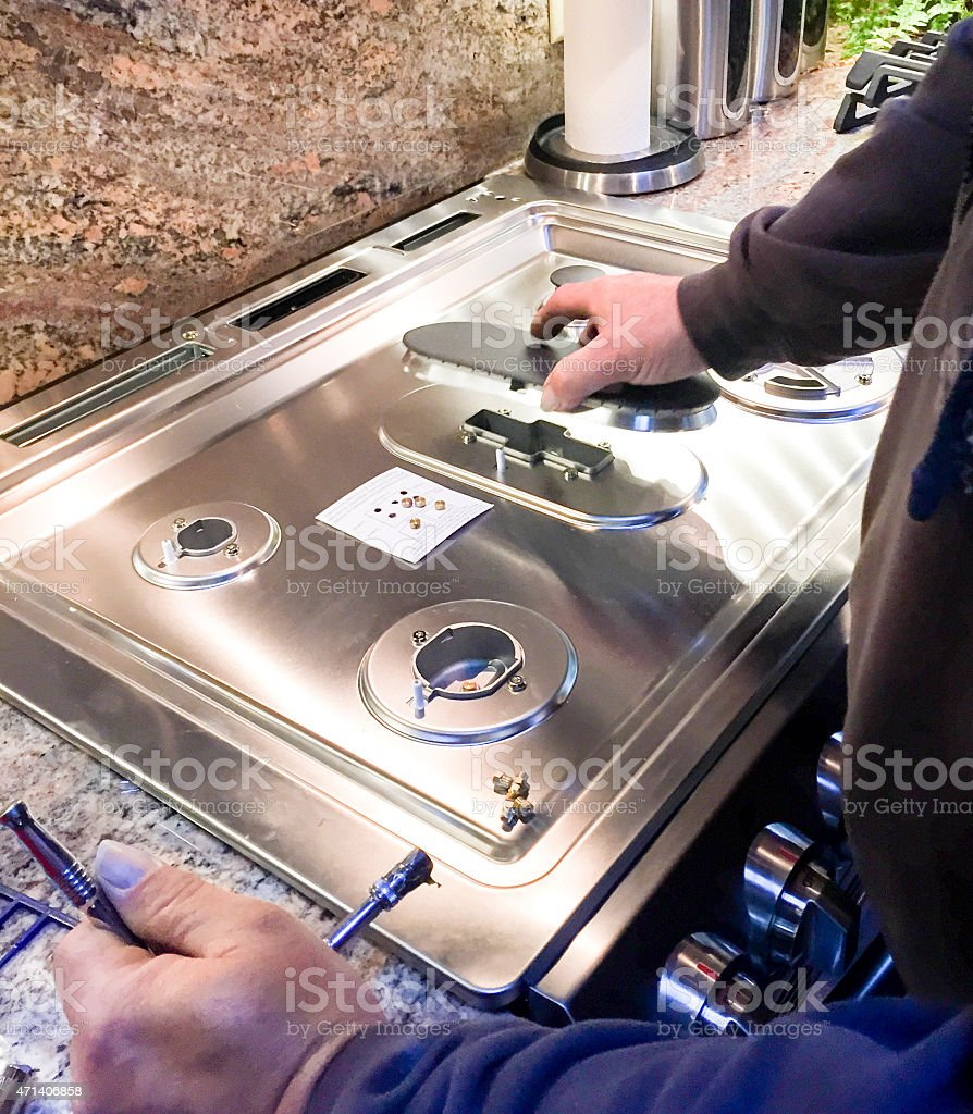 Installing Propane Jets on stove in kitchen stock photo