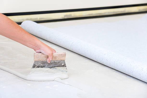Installing PVC floor Laying Tarkett floor. Spreading Adhesive. linoleum stock pictures, royalty-free photos & images