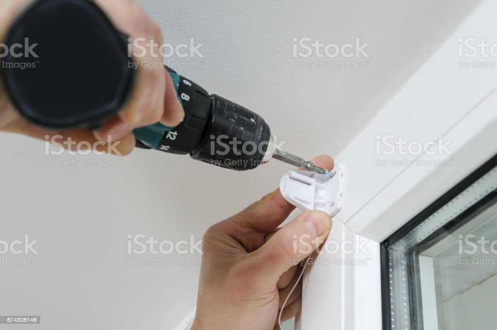 Installing roller blind on a window. stock photo