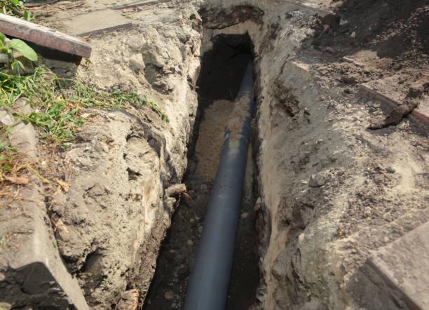 Het installeren van rioolbuis in de grondgeul. Huis rioolafvoerpijp installatie foto
