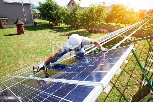 istock Installing solar panels on house's green carcass. 1008854276
