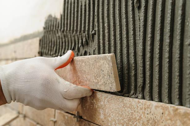 installing the tiles on the wall. - fliesenkleber stock-fotos und bilder
