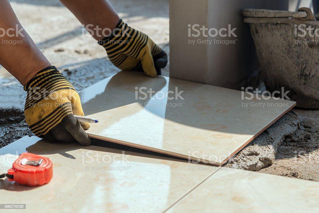 Installing tiles floor in construction work stock photo