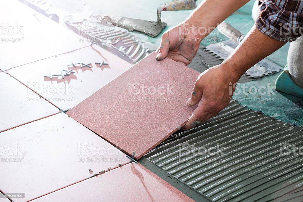 Installing Tiles - Professional Worker stock photo