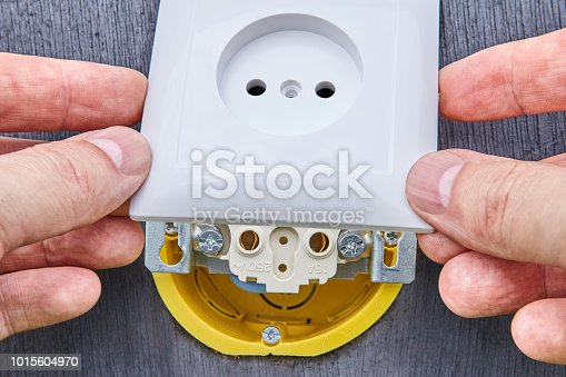 1015605026 istock photo Installing top panel on household electrical socket. 1015604970