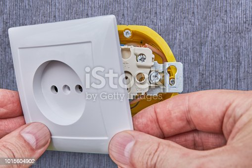 1015605026 istock photo Installing top panel to household power supply network outlet. 1015604902