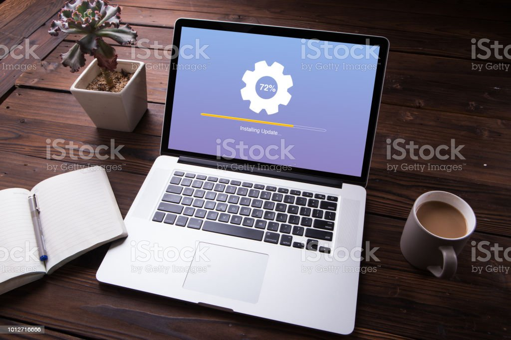 Installing update process with gearbox percentage progress and loading bar on laptop / computer with office equipment on wooden desk background - Foto stock royalty-free di Aggiornamento Software