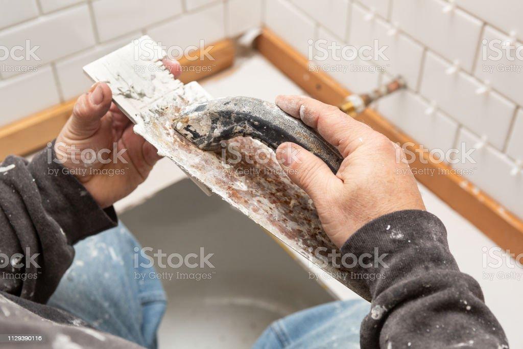 Installing White subway tile stock photo