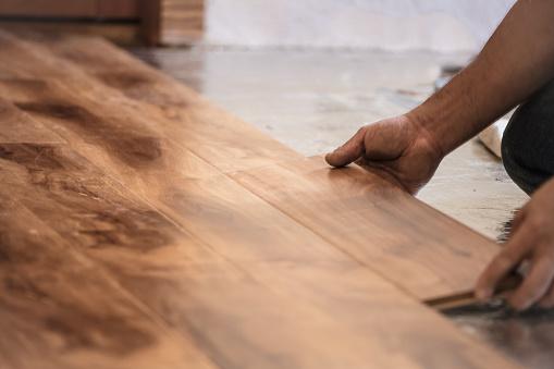 Man installing wood flooring in home.