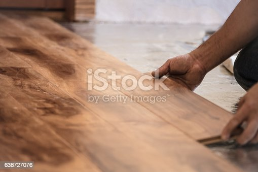 Man installing wood flooring in home.
