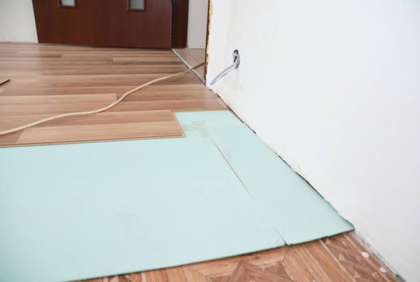 Het installeren van houten laminaatvloeren met isolatie- en geluidsisolatieplaten. foto