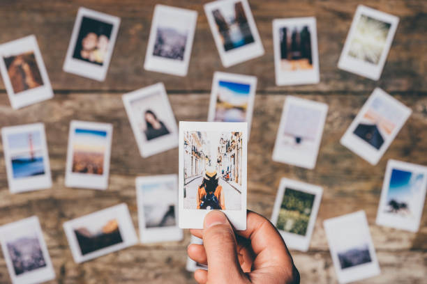 Instant camera prints on a table - foto stock