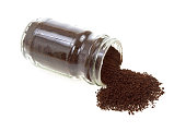 Side view of a glass jar of instant coffee with some of the granules spilling onto a white background.