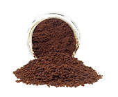 A glass jar with instant coffee spilling out in front.