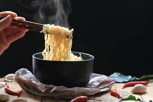 instant noedels en lepel met houten vork in cup met rook stijgt en knoflook op een donkere achtergrond, natrium dieet hoog risico nierfalen, gezond eten concept - ramen noedels stockfoto's en -beelden