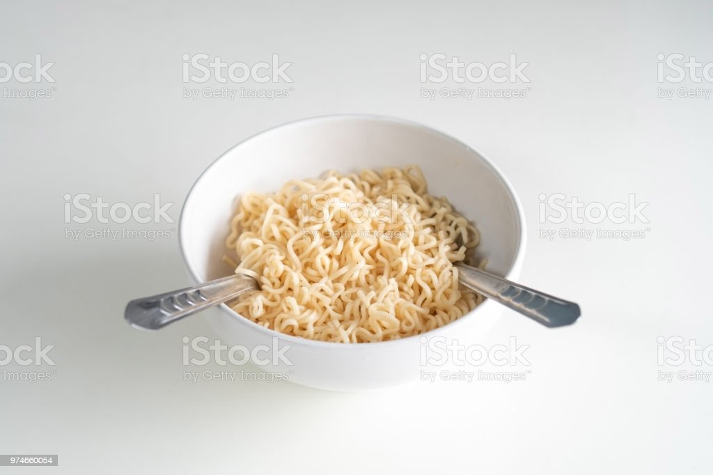 Instant noodles ready to eaton in the bowl with fork and spoon on white table wooden. stock photo