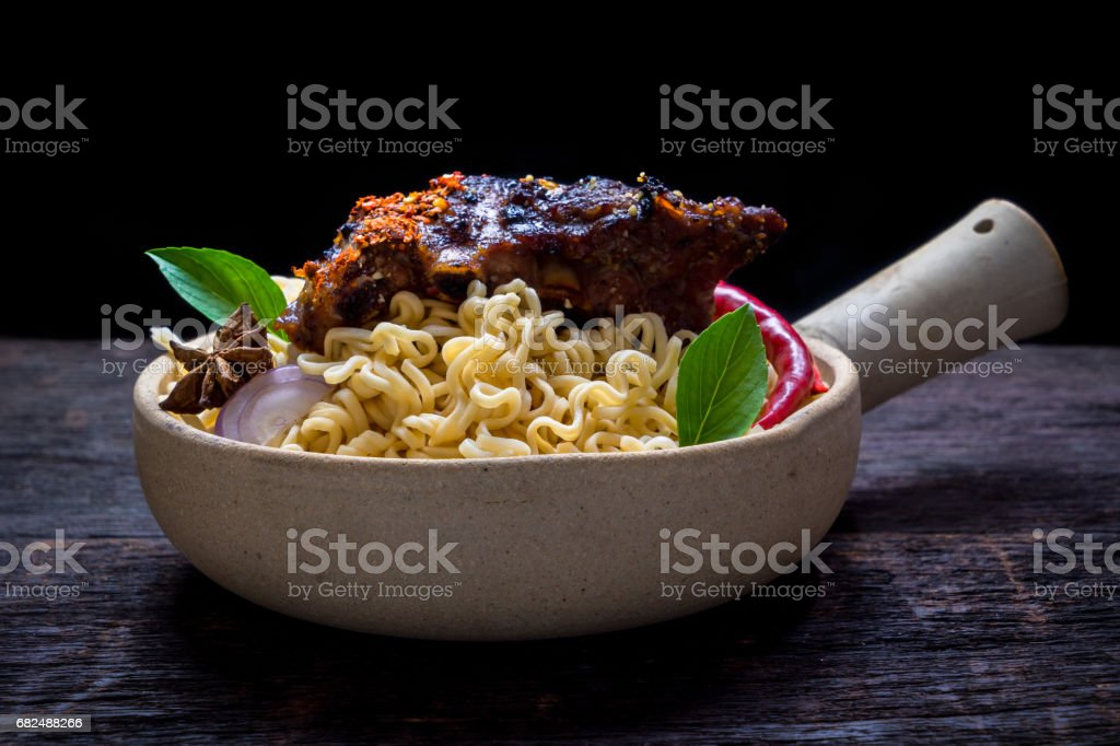 Instant noodles with roast pork spareribs in the clay pot on wooden background Стоковые фото Стоковая фотография