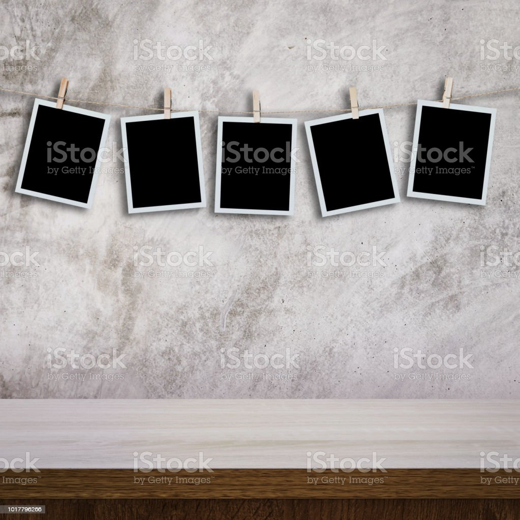 Instant Photo Hanging On Wood Table And Cement Wall Texture