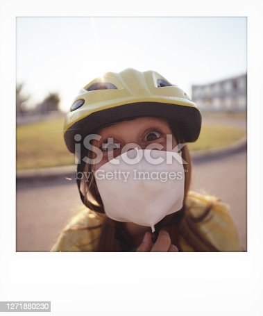 Instant photo of a schoolgirl wearing a protective face mask in front of the school building on a bright sunny day; going back to school during the COVID-19 pandemic.