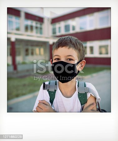 Instant photo of a schoolboy wearing a protective face mask in front of the school building on a bright sunny day; going back to school during the COVID-19 pandemic.