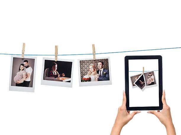 drucke instant fotos hängen am seil und digitale tablet - hochzeitsbilder stock-fotos und bilder