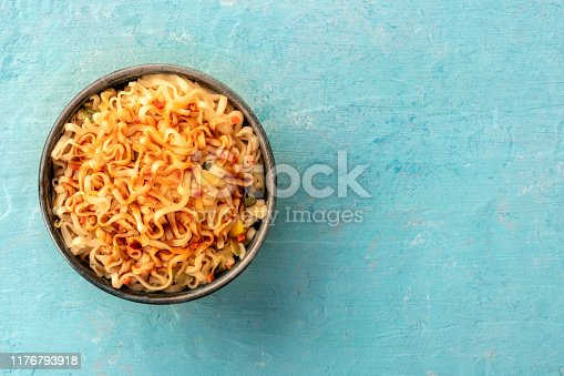 Instant soba noodles with carrot and a sauce, top shot on a teal blue background with a place for text